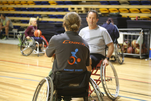 Andrew. Wallace MP sitting in a wheelchair playing basketball
