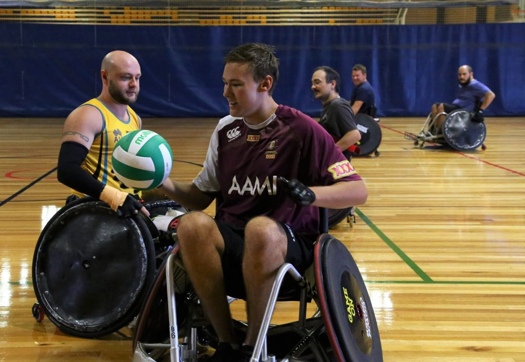 two rugby players in wheelchairs passing the ball