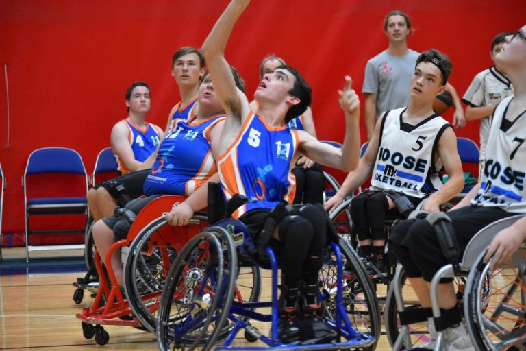 Group of basketballers in chairs reaching for ball