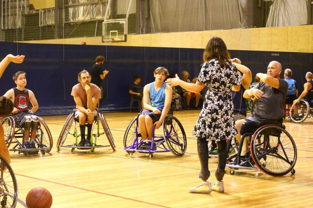 team leader instructing group of participants sitting in a circle in their chairs all listening intently