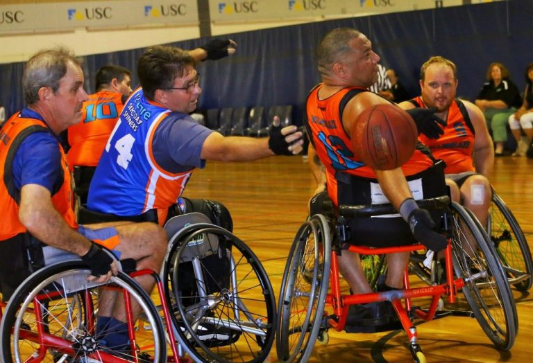 group of male players reaching to grab basketball