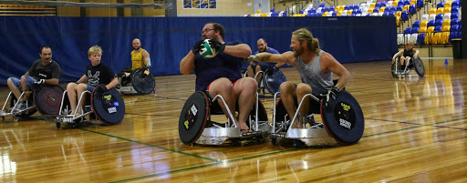 group of men and boys in wheelchairs playing rugby